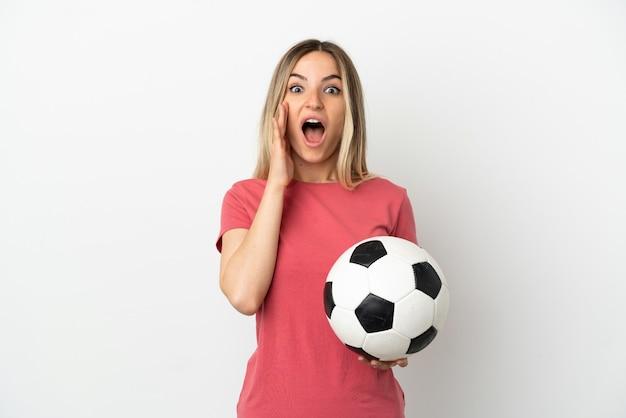 Молодая женщина-футболист над изолированной белой стеной с удивленным и шокированным выражением лица