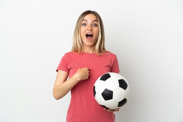 Молодой футболист женщина над изолированной белой стеной с удивленным выражением лица