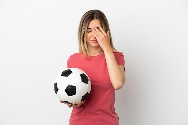 Молодая женщина-футболист над изолированной белой стеной с усталым и больным выражением лица