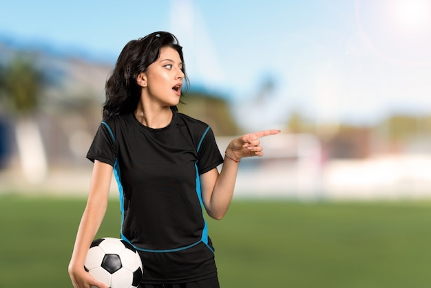 Young football player woman surprised and pointing finger to the side at outdoors