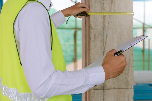 Young foreman builder engineer or inspector checking and inspecting with clipboard and measuring tape at construction site building