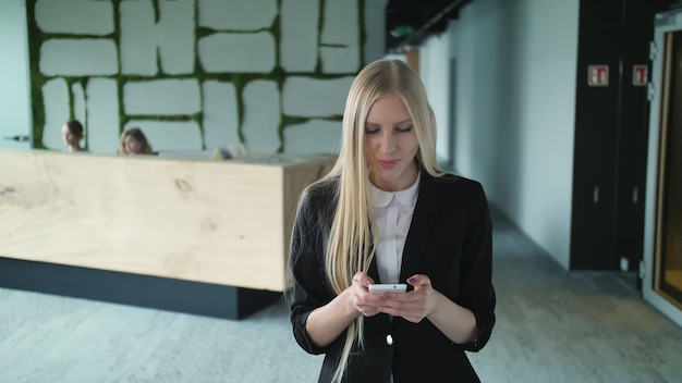 Young formal woman using smartphone in office.