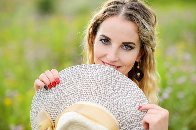 그녀의 손에 밀짚 모자와 젊은 주근깨가 여자. 야외 포즈 백인 웃는 소녀.