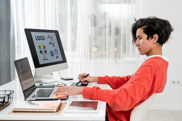 Молодой дизайнер-фрилансер использует ноутбук, сидя за столом перед монитором компьютера и делая логотип