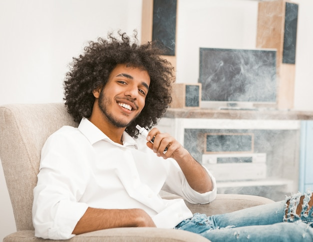 Young freelance man relaxes while smoking e-cigarette. shaggy macho charmingly smiles while looking at the camera. toned image