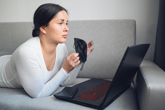 Молодая независимая женщина в маске медицины стороны звоня видео- с компьтер-книжкой на сером кресле во время карантина дома изоляции коронавируса. covid-19 пандемический вирус corona. онлайн работа из дома концепции.