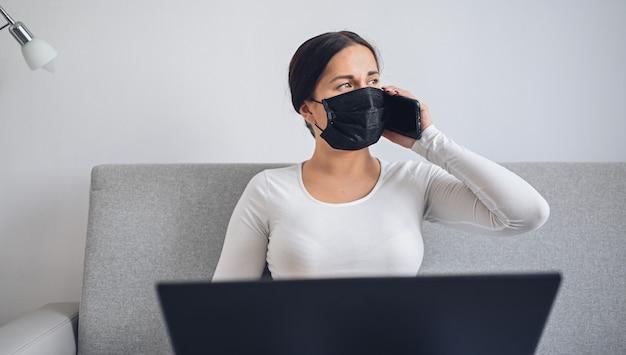 Молодая независимая женщина в маске медицины стороны работая на компьтер-книжке и телефоне на сером кресле во время карантина дома изоляции коронавируса. covid-19 пандемический вирус corona. онлайн работа из дома концепции.