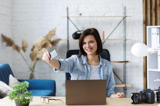 Молодой фрилансер в домашнем офисе с кредитной картой и ноутбуком