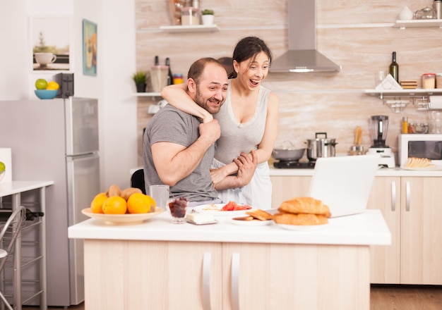 若いフリーランサーは、朝食をとり、キッチンでラップトップに取り組んでいる間、良いニュースを読みます。朝の自宅で成功した大喜びの陶酔起業家、勝者とビジネスの勝利