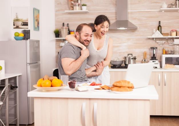 Il giovane libero professionista legge buone notizie mentre fa colazione e lavora al computer portatile in cucina. imprenditore euforico felicissimo di successo a casa al mattino, vincitore e trionfo degli affari