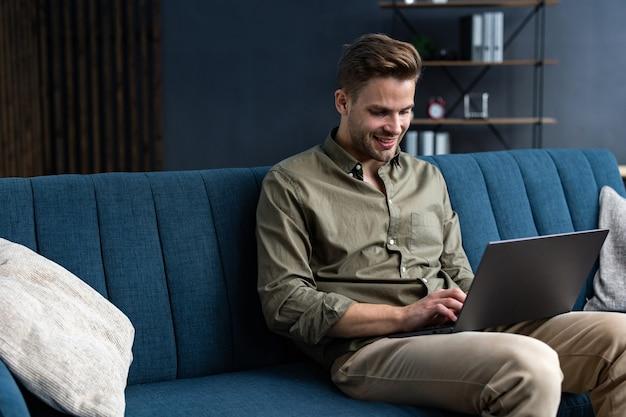 Молодой фрилансер, работающий дома с ноутбуком. отправка текстовых сообщений, просмотр интернета. обучение онлайн, онлайн-обучение, удаленная работа. молодые люди работают дома. бизнес-концепция.