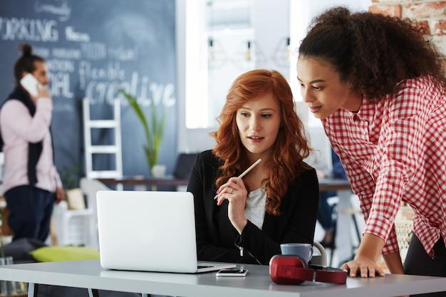 Молодые фрилансеры, использующие ноутбук в современном коворкинг-офисе