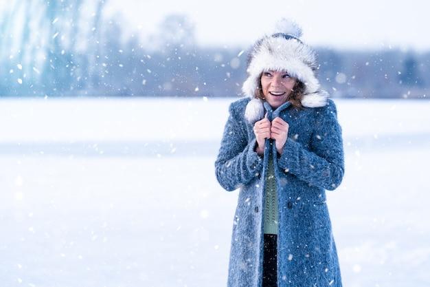 Молодая замерзающая женщина на зимнем ледяном озере