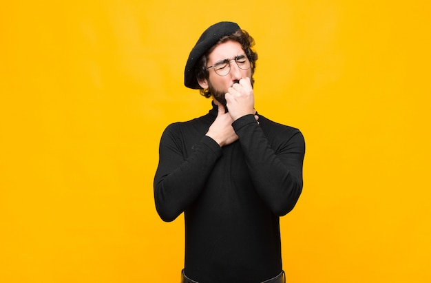 Young french artist man feeling ill with a sore throat and flu symptoms, coughing with mouth covered against orange wall