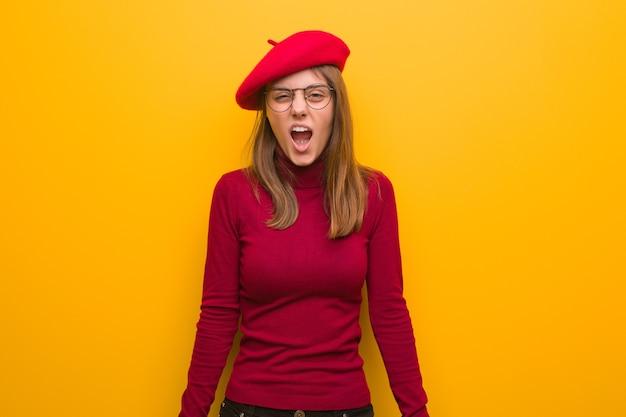 非常に怒っていると積極的に叫んでいる若いフランス人アーティストの女性