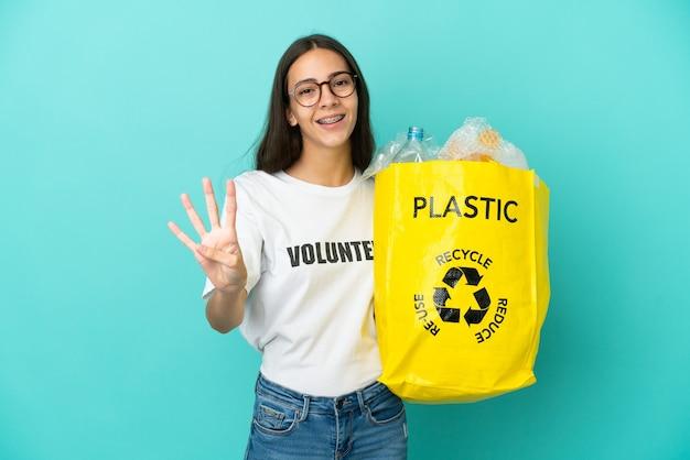 Молодая француженка с сумкой, полной пластиковых бутылок, счастлива и считает четыре пальцами