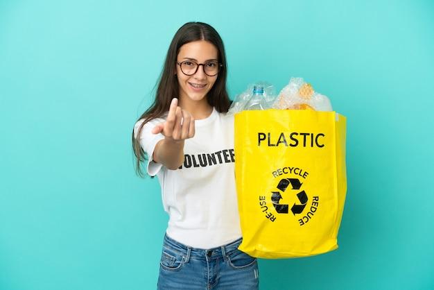 Молодая француженка держит сумку, полную пластиковых бутылок, которые нужно переработать, приглашая прийти с рукой. счастлив что ты пришел