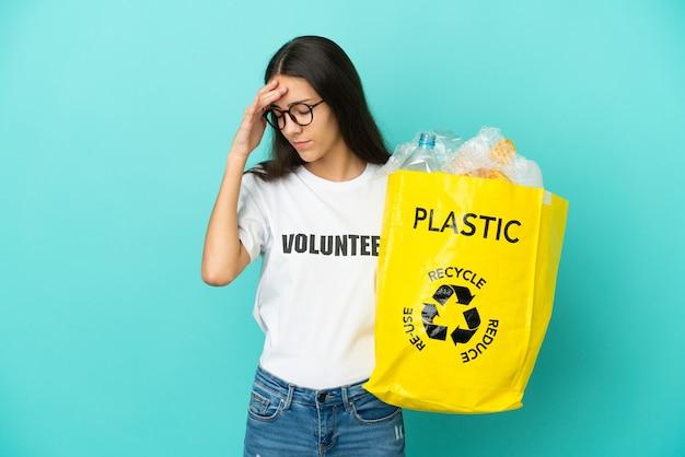 Молодая француженка с головной болью держит мешок, полный пластиковых бутылок, которые нужно переработать