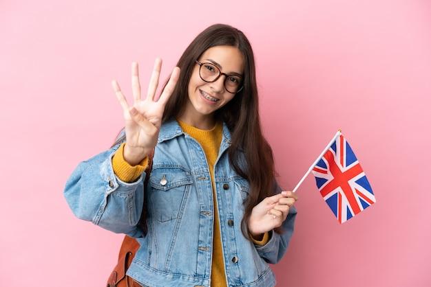 Молодая французская девушка держит флаг соединенного королевства, изолированную на розовом фоне, счастлива и считает четыре пальцами