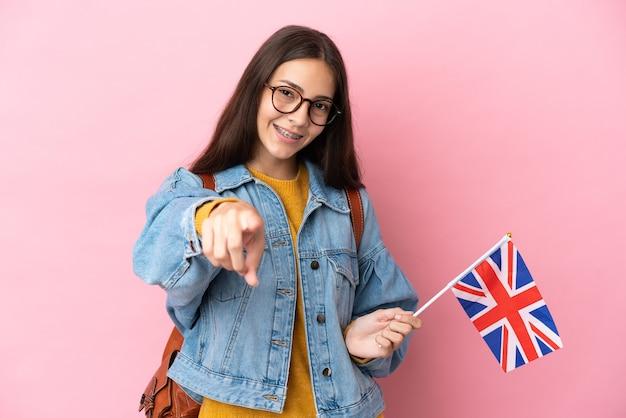 행복 한 표정으로 앞을 가리키는 분홍색 배경에 고립 된 영국 국기를 들고 젊은 프랑스 소녀