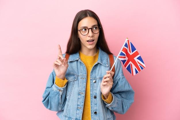 손가락을 가리키는 아이디어를 생각하는 분홍색 배경에 고립 된 영국 국기를 들고 젊은 프랑스 소녀