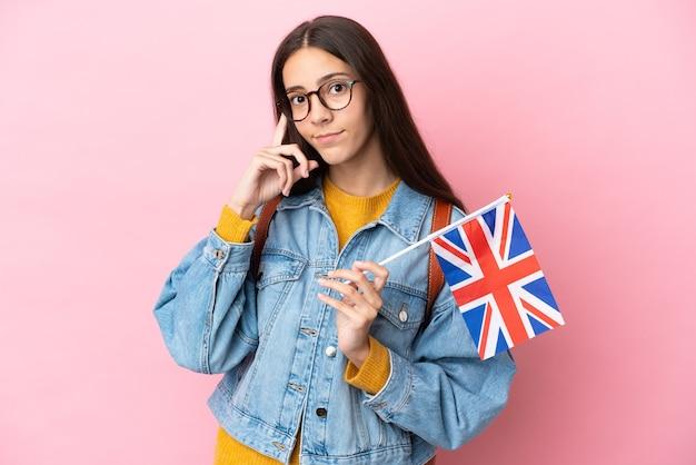 아이디어를 생각하는 분홍색 배경에 고립 된 영국 국기를 들고 젊은 프랑스 소녀
