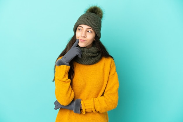 Young french girl isolated on blue background with winter hat having doubts while looking up