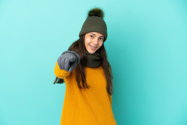 Young french girl isolated on blue background with winter hat pointing front with happy expression