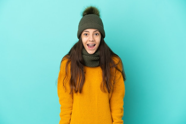 Young french girl isolated on blue background with winter hat with surprise facial expression