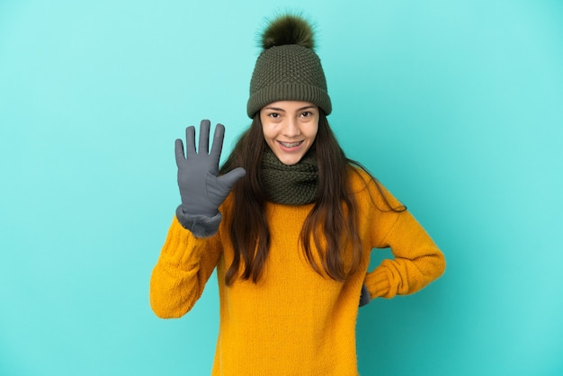 손가락으로 5 세 겨울 모자와 파란색 배경에 고립 된 젊은 프랑스 소녀