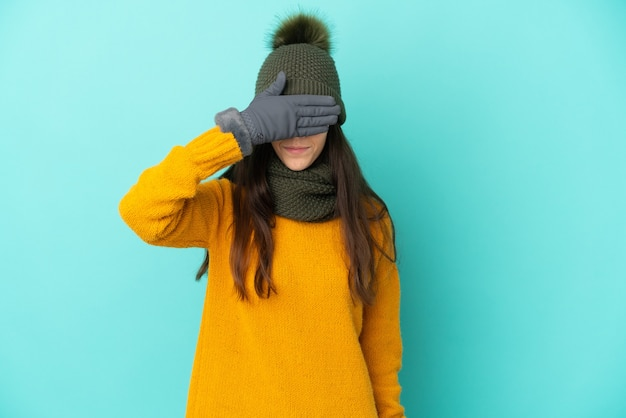 Молодая французская девушка, изолированные на синем фоне с зимней шапкой, закрывающей глаза руками. не хочу что-то видеть
