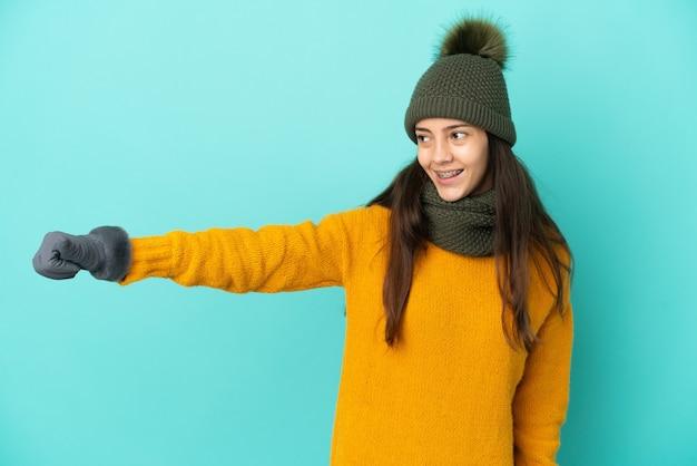 Молодая французская девушка изолирована на синем фоне с зимней шапкой, показывая жест рукой вверх
