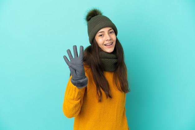 Молодая французская девушка изолирована на синем фоне в зимней шапке счастлива и считает четыре пальцами