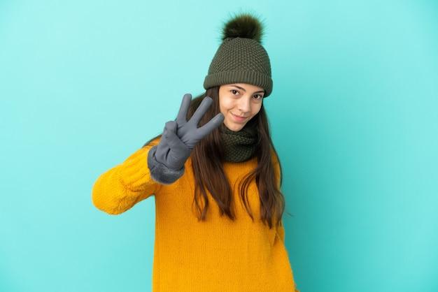 Молодая французская девушка изолирована на синем фоне в зимней шапке счастлива и считает три пальцами