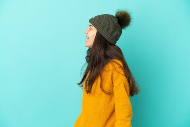 Молодая французская девушка изолирована на синем фоне в зимней шапке, смеясь в боковом положении