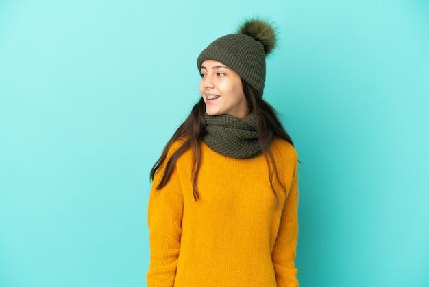 Молодая французская девушка изолирована на синем фоне в зимней шапке, глядя в сторону и улыбаясь
