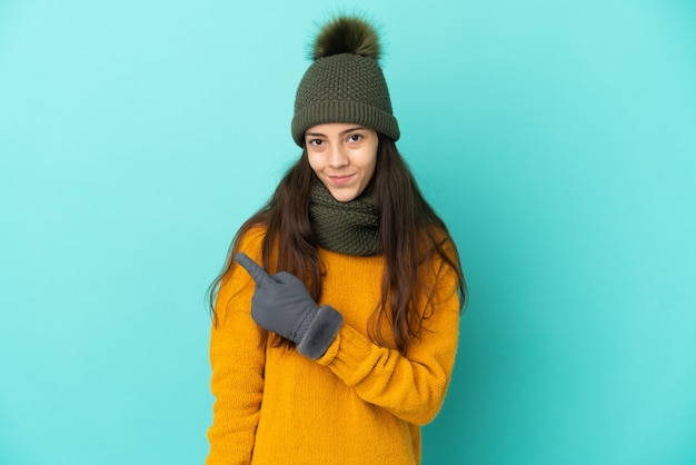 Молодая французская девушка изолирована на синем фоне с зимней шапкой, указывая в сторону, чтобы представить продукт