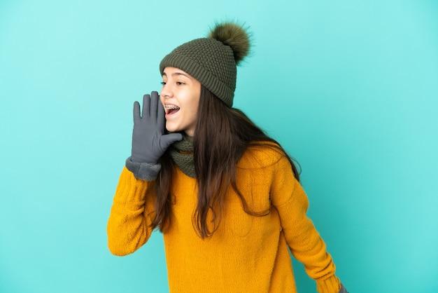 Молодая французская девушка изолирована на синем фоне в зимней шапке и кричит с широко открытым ртом