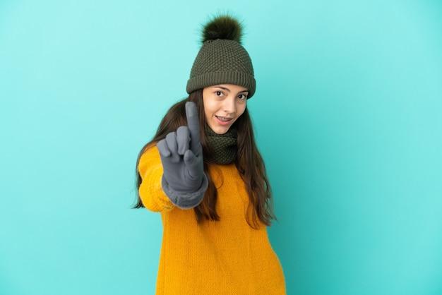 Молодая французская девушка изолирована на синем фоне с зимней шапкой, показывая и поднимая палец