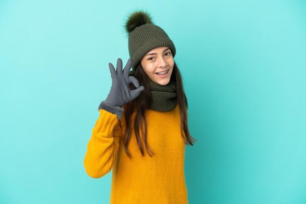 Молодая французская девушка изолирована на синем фоне с зимней шапкой, показывая пальцами знак ок