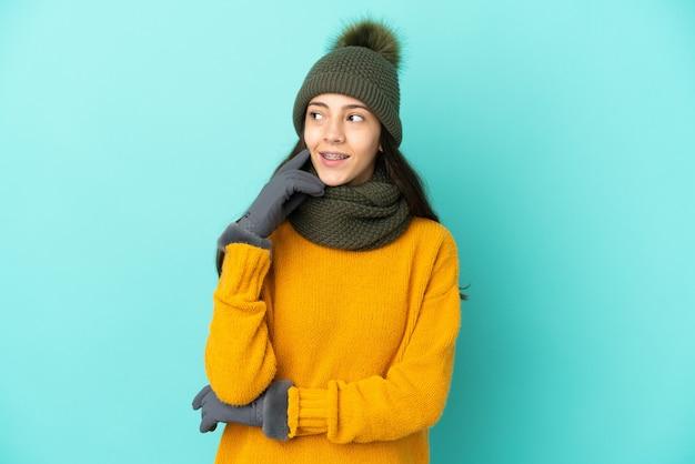 Молодая французская девушка изолирована на синем фоне в зимней шапке, думая об идее, глядя вверх