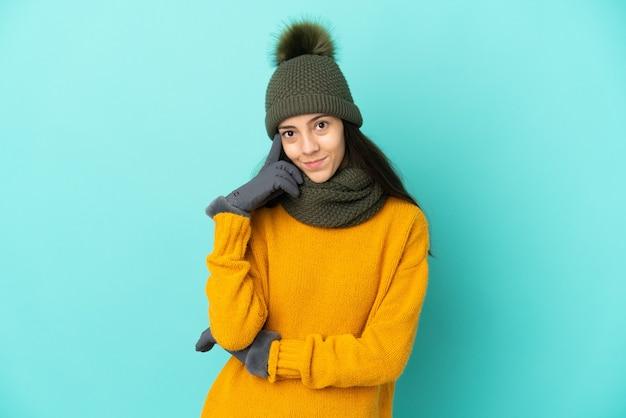Молодая французская девушка изолирована на синем фоне в зимней шапке, думая об идее