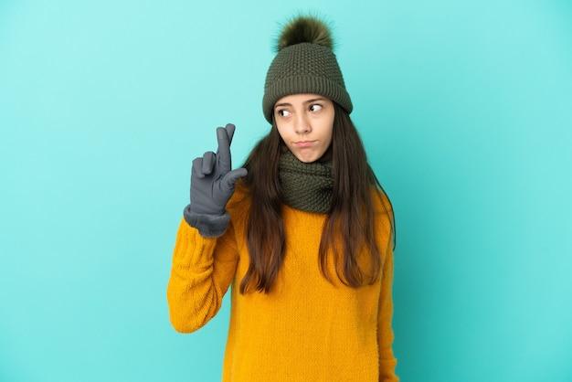 Молодая французская девушка изолирована на синем фоне в зимней шапке со скрещенными пальцами и желает лучшего