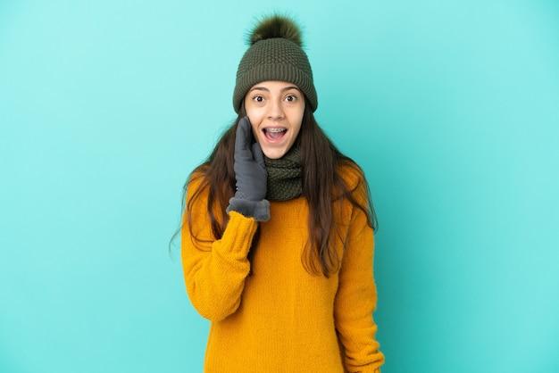 Молодая французская девушка изолирована на синем фоне в зимней шапке с удивлением и шокированным выражением лица