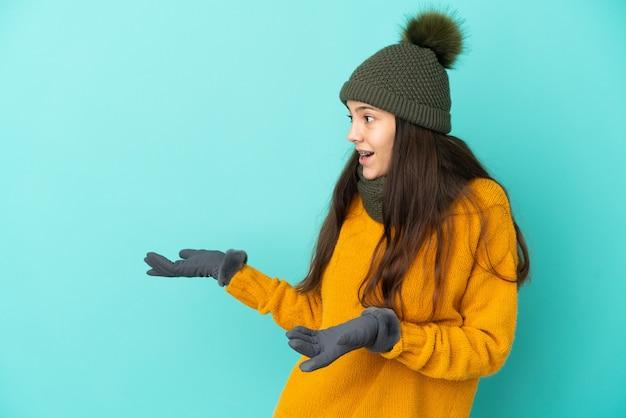 Молодая французская девушка изолирована на синем фоне в зимней шапке с удивленным выражением лица, глядя в сторону