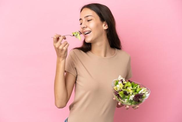Молодая французская девушка изолирована на розовом фоне, держа миску салата и глядя на нее со счастливым выражением лица