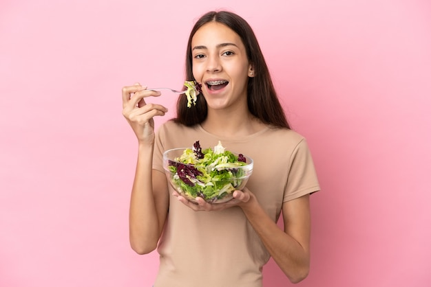 Молодая французская девушка изолирована на розовом фоне, держа миску салата с счастливым выражением лица