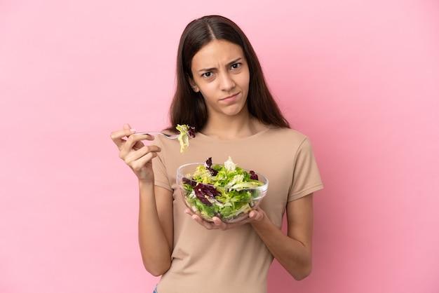Молодая французская девушка изолирована на розовом фоне, держа миску салата с грустным выражением лица