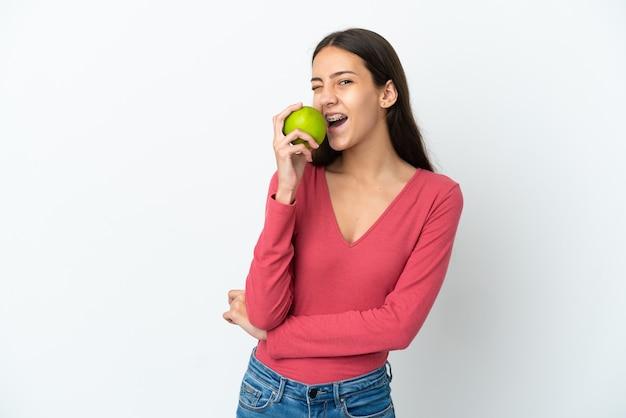 リンゴを食べる白い背景で隔離の若いフランスの女の子