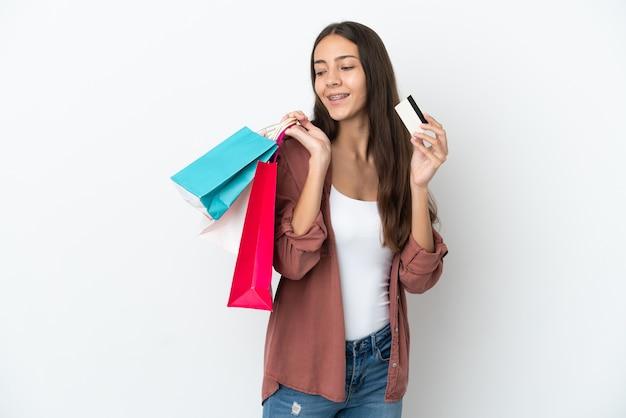 Молодая французская девушка изолирована на белом фоне, держа хозяйственные сумки и кредитную карту